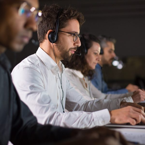 Side view of confident call center operator talking with client. Caucasian young man in eyeglasses typing on laptop while serving client. Call center concept