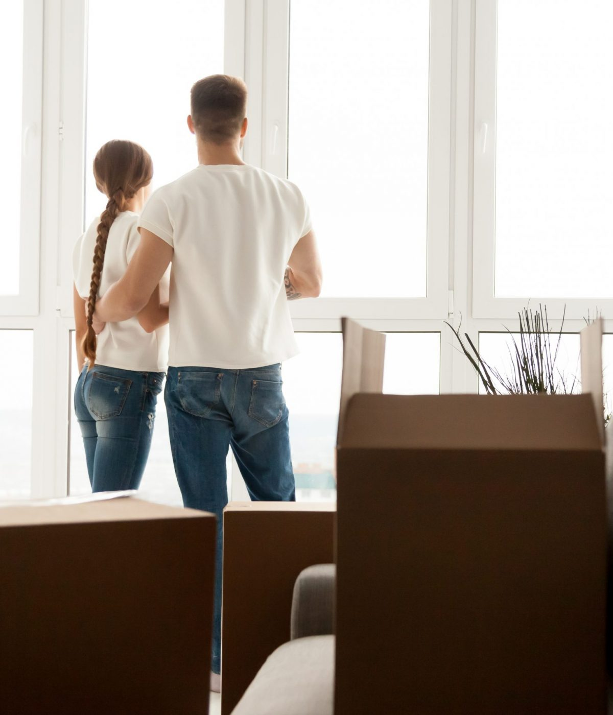 Millennial couple stand near window looking far away after moving in to new home with cardboard boxes, husband and wife plan future together, hugging seeing new perspectives. New beginning concept