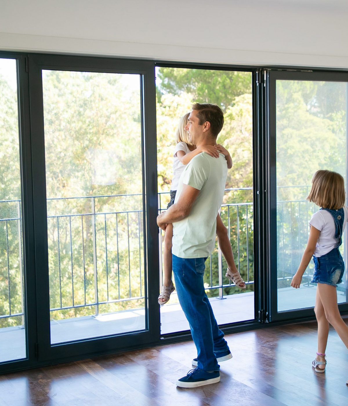 Happy father with daughter standing near open balcony and smiling. Blonde mother holding girl hand and talking with her. Enjoying family watching new house or flat. Relocation and mortgage concept